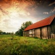 Stock Photo: Sunset by an old barn