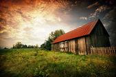 Coucher du soleil par une ancienne grange — Photo