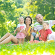 Happy young couple with their children have fun at park — Stock Photo #6768611