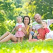 Happy young couple with their children have fun at park — Stock Photo #6769001