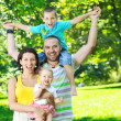 Happy young couple with their children have fun at park — Stock Photo #6769226