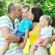 Happy young couple with their children have fun at park — Stock Photo #6771378