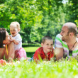 Happy young couple with their children have fun at park — Stock Photo #6771396