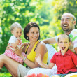 Happy young couple with their children have fun at park — Stock Photo #6771462