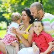 Happy young couple with their children have fun at park — Stock Photo #6772839