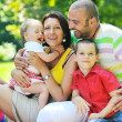 Happy young couple with their children have fun at park — Stock Photo #6782870