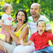 Happy young couple with their children have fun at park — Stock Photo #6782969