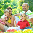 Happy young couple with their children have fun at park — Stock Photo #6783018