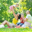 Happy young couple with their children have fun at park — Stock Photo #6783420