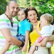 Happy young couple with their children have fun at park — Stock Photo #6783962