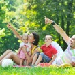Happy young couple with their children have fun at park — Stock Photo #6784159