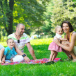 Happy young couple with their children have fun at park — Stock Photo #6785087