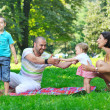 Happy young couple with their children have fun at park — Stock Photo #6786403