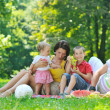 Happy young couple with their children have fun at park — Stock Photo #6786568