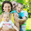 Happy young couple with their children have fun at park — Stock Photo #6789453