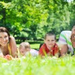 Happy young couple with their children have fun at park — Stock Photo #6789736