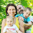 Happy young couple with their children have fun at park — Stock Photo #6789951