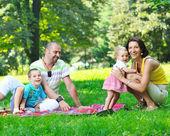 Casal jovem feliz com seus filhos se divertir no parque — Fotografia Stock