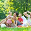 Happy young couple with their children have fun at park — Stock Photo #6790155