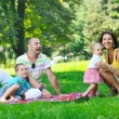 Happy young couple with their children have fun at park — Stock Photo #6792155