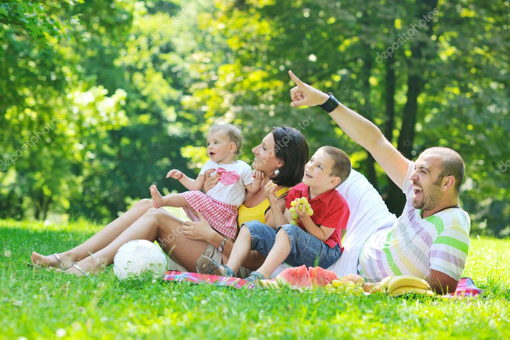 Happy young couple with their children have fun at beautiful park outdoor in nature — Stock Photo #6790923