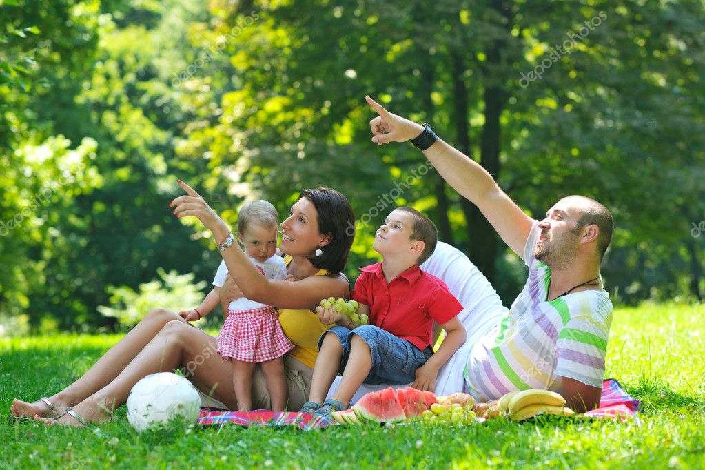 Happy young couple with their children have fun at beautiful park outdoor in nature — Stock Photo #6791331