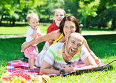 Happy young couple with their children have fun at park — Стоковое фото