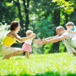 Happy young couple with their children have fun at park — Stock Photo #6815397