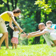 Happy young couple with their children have fun at park — Stock Photo #6815597