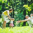 Happy young couple with their children have fun at park — Stock Photo #6816754