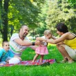 Happy young couple with their children have fun at park — Stock Photo #6819424