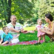 Happy young couple with their children have fun at park — Stock Photo #6819461
