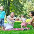 Happy young couple with their children have fun at park — Stock Photo #6819481