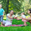 Happy young couple with their children have fun at park — Stock Photo #6819494