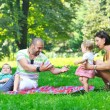 Happy young couple with their children have fun at park — Stock Photo #6819512