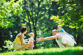 Happy young couple with their children have fun at park — Stockfoto