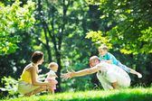 Happy young couple with their children have fun at park — Stock fotografie