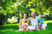 Happy young couple with their children have fun at park — Foto Stock