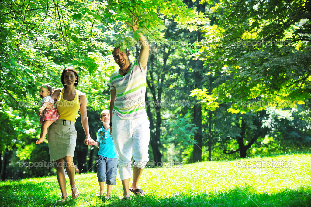 Happy young couple with their children have fun at beautiful park outdoor in nature — Stock Photo #6817158