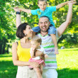 Happy young couple with their children have fun at park — Stock Photo #6820471