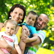 Happy young couple with their children have fun at park — Stock Photo #6820798