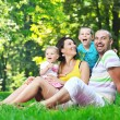 Happy young couple with their children have fun at park — Stock Photo #6821403