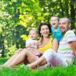 Happy young couple with their children have fun at park — Stock Photo #6821495