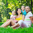 Happy young couple with their children have fun at park — Stock Photo #6821621