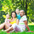 Happy young couple with their children have fun at park - Stock Photo