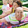 Happy young couple with their children have fun at park — Stock Photo #6821823