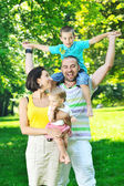 Happy young couple with their children have fun at park — Stok fotoğraf