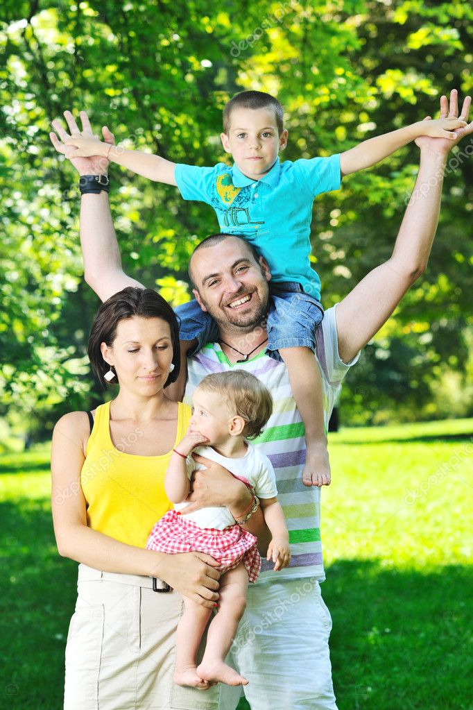 Happy young couple with their children have fun at beautiful park outdoor in nature  Stock Photo #6820646