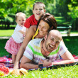 Happy young couple with their children have fun at park — Stock Photo #6833561