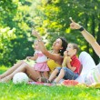 Happy young couple with their children have fun at park — Stock Photo